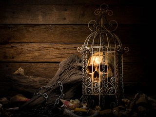 Still life art image of humen skull in white cage surrounding with pile of bones and metal chain and old wood on wooden table and background with dim light for Halloween night