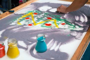 Sand animation, drawing sand closeup, girl draws a Christmas tree on the sand.