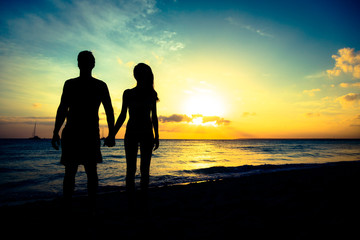 Young Couple Enjoying Sunset By The Beach