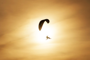 Powered paragliding flying against the backdrop of the setting sun