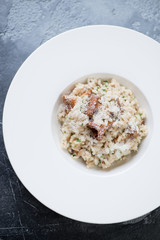 Above view of risotto with chanterelles and parmesan in a white plate, vertical shot
