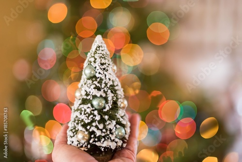 tiny christmas tree in a womans hand in front of brightly colored bokeh lights with copy