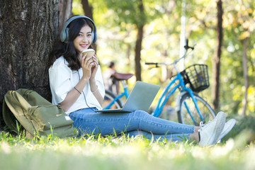Asian Woman holding coffee with attractive smiling at garden. People lifestyle concept.
