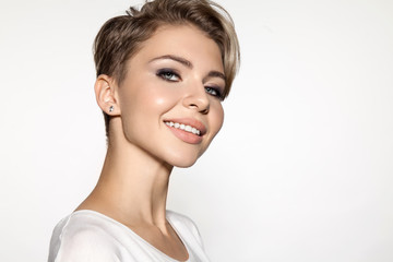 Attractive young lady smiling and look at camera, portrait isolated on white. Close up portrait of girl with blonde short hair. Young female model in white T-shirt. Concept of beauty and fashion.