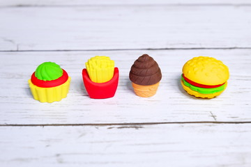 Concept of fast food of burger,french fries,and cake in kids eraser form on wooden background.