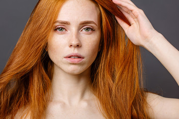 beautiful redhead woman holding her healthy and shiny hair, studio gery
