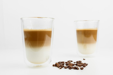 Two Hot Coffee Drinks With Milk With Coffee Beans On White Background