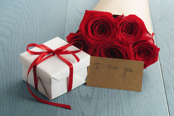 gift box with red roses bouquet and i love you paper card on blue wood table