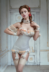 Red head curly hair woman dressed in renaissance corset with choker posing at camera