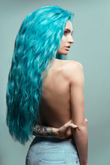 Beautiful woman with curly blue hair and tattoos posing at camera against blue background, back view