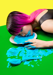 Woman laying on floor with face on plate with blue liquid