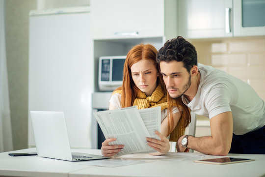 Worried couple paying their bills online with laptop at home in the living room