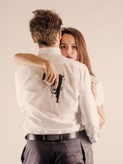 A cute guy and a girl are standing with a gun. Secret Service. White background.