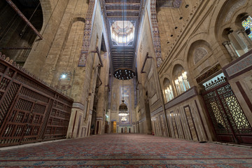 Interior of al Rifai mosque with old decorated bricks stone wall, colored marble decorations, wooden ornate ceiling, big brass chandeliers, and wooden latticework door, Cairo, Egypt