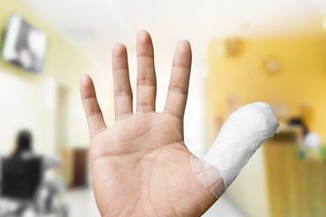 thumb with bandage with abstract blur of hospital interior background.