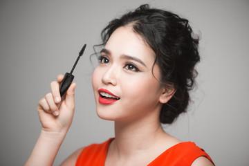 Beautiful young asian woman doing makeup using mascara on her eyelashes