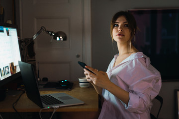 Woman with phone at laptop