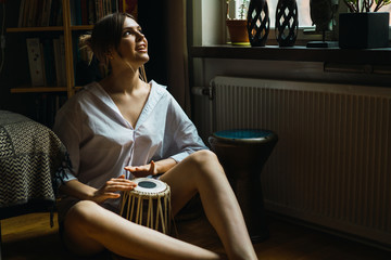Young woman playing percussion while sitting on floor