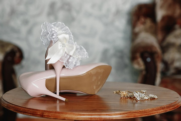 bride's biege shoes on heel on a carpet.