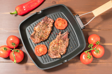 Grilled steak on grill pan with tomatoes on dark background
