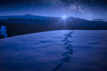 Beautiful winter night in a carpathian mountain valley with many stars in a sky