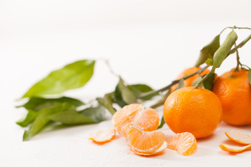 Peeled tangerines and peel with leaves on white background