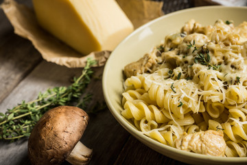 Fresh pasta with meat, mushrooms and herbs. On the rustic wooden background. Selective focus.