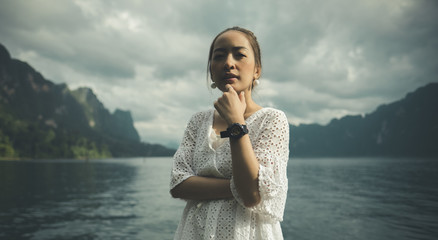woman in white dress standing in mountain lake posing looking to camera