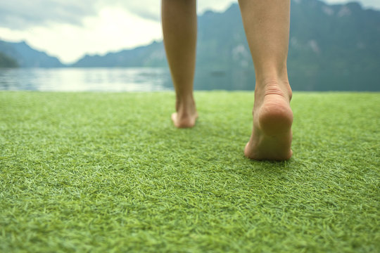 Young female legs walking towards the sunset on a ground grass with blur mountain and lake
