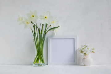 Mockup with a white frame and white daffodils