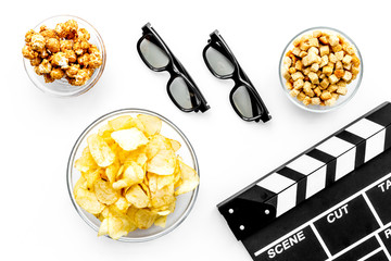 Fast food for watching film. Popcorn, crisps, rusks near glasses and clapperboard on white background top view