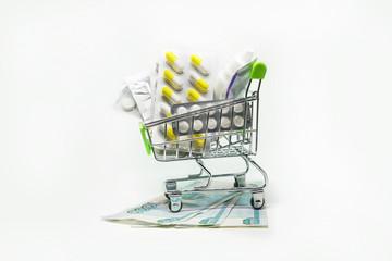 Shopping cart full of drug and medicine pills on rubles money