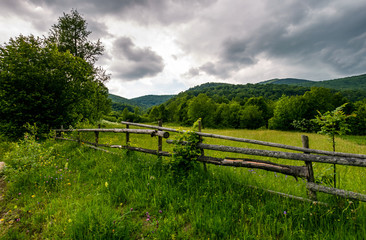 wooden fence on a rural meadow in mountains. lovely agriculture scenery on a cloudy summer day