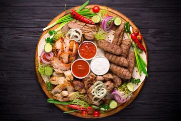 Assorted grilled meat and vegetables on rustic wooden table