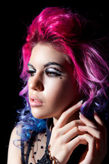 The girl with pink hair and fantasy makeup looks to the side on a black isolated background close-up