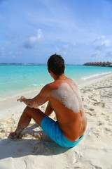 man in blue shorts with sand on his back sits on white sand tropical island