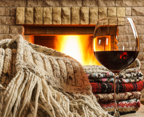 Glass of  red wine before cozy fireplace.