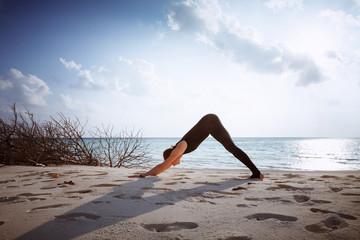 woman in black jumpsuit doing yoga Sun salutation Surya Namaskar