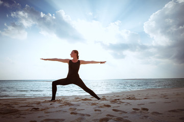 young girl standing in yoga warrior asana on dreamlike beach on summer vacation