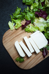 Greek feta cheese on a wooden board, lettuce leaves on a black background.
