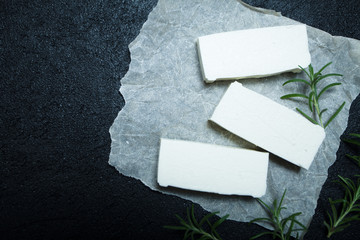 Fresh organic feta cheese with rosemary on white paper, top view. Space for text.
