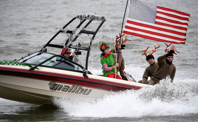 People dressed as Santa's reindeer wave as one of them, dressed as a Santa's elf, holds an American flag during an annual Christmas Eve performance on the Potomac River, Alexandria, Virginia