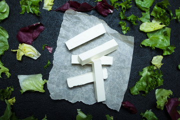 Feta cheese sticks, lettuce leaves on a black background.