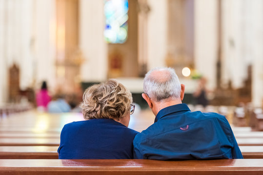Back view of an elderly couple in the church, Madrid, Spain. Copy space for text.