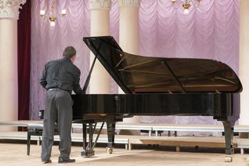A man in black tunes a black grand piano