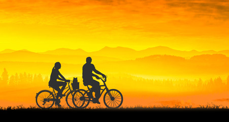 Young couple and dog riding bicycles at sunset