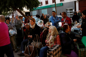 People listen to instructions from a volunteer as they wait to receive food during a daily food distribution organised by the non-governmental organisation Angeles Malaguenos de la noche on Christmas eve in Malaga
