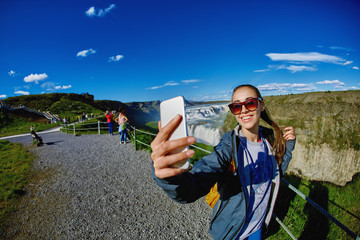 smiling woman making selfie on a Gullfoss waterfall background
