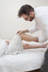 Lekarz ortopeda bada kolano starej kobiety leżącej na łóżku.