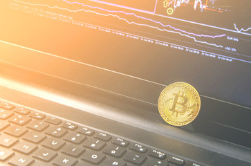 Bitcoin coin placed on modern black notebook . Close-Up photo Bitcoin , exchange virtual value, crypto digital money . Background Live Stock trading through internet .Selling big amounts, real estate.